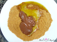 Añadiendo a las galletas trituradas la mantequilla y la nutella