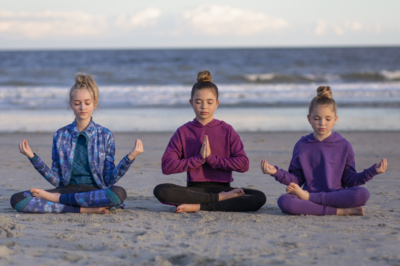 tween girls doing yoga poses on the beach