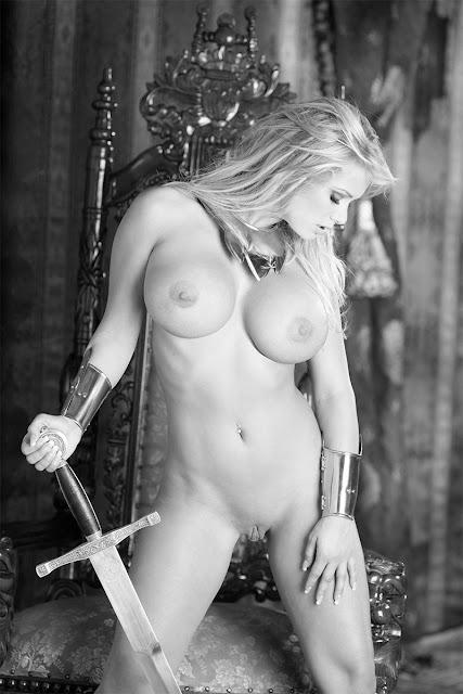 Bild av naken fitness tjej med silikonbröst, rakad fitta och ett blankt svärd