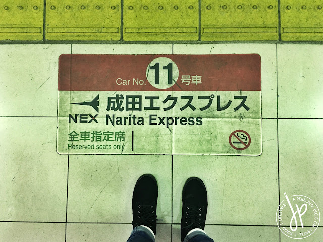 train platform sign, pair of black boots, feet