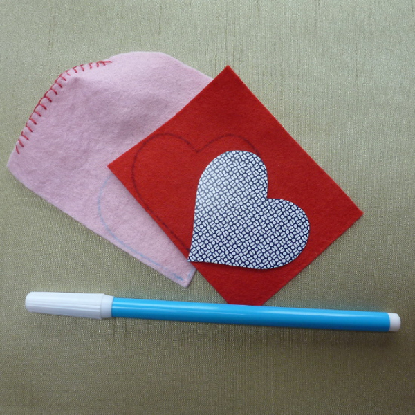 Water soluble blue fabric marker pen tracing around a heart template onto red and pink felt fabric