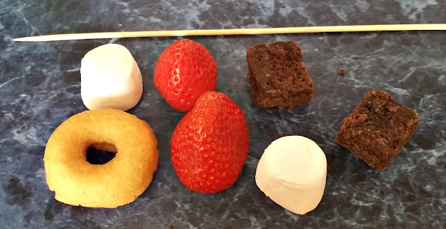a mini doughnut, strawberries, marshmallows, brownies and the wooden skewer
