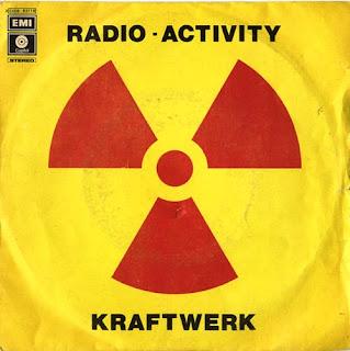 Tono: Radio-Activity, Kraftwerk. Portada del single de 1975. La imagen muestra el símbolo de peligro de la radioactividad con fondo amarillo. Dicho símbolo, también llamado trébol radiactivo, consta de un punto rojo central del que parten tres haces en forma de porción de quesito, separados 120 grados entre sí, de color rojo intenso