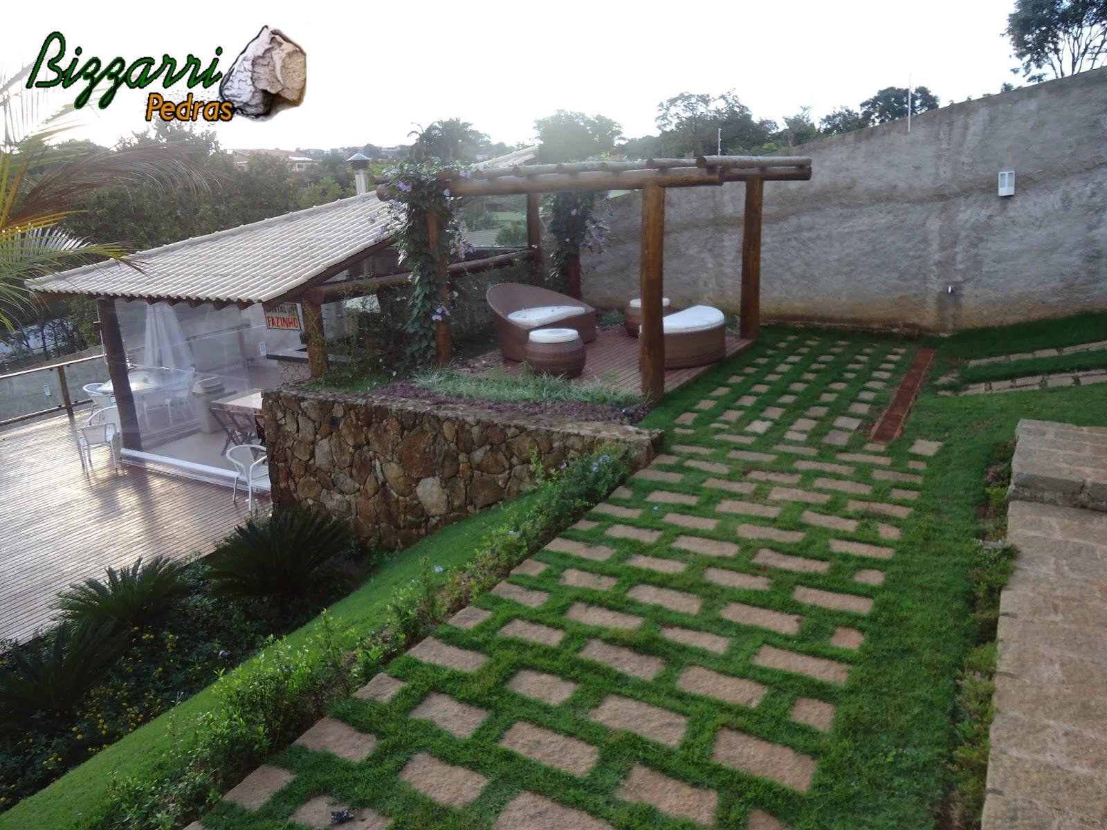 Calçamento com pedras folhetas com junta de grama esmeralda junto com o pergolado de madeira de eucalipto tratado.