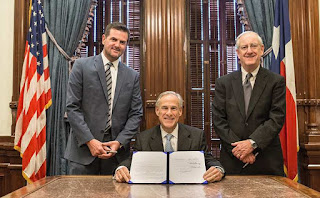 Texas Gov. Greg Abbott (center) signed a bill today that prevents taxpayers from having to pay for abortions through their insurance plans.