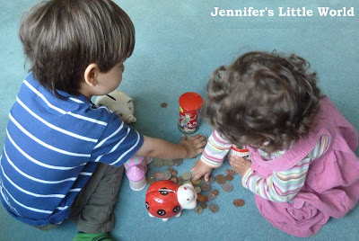 Children posting coins in money boxes
