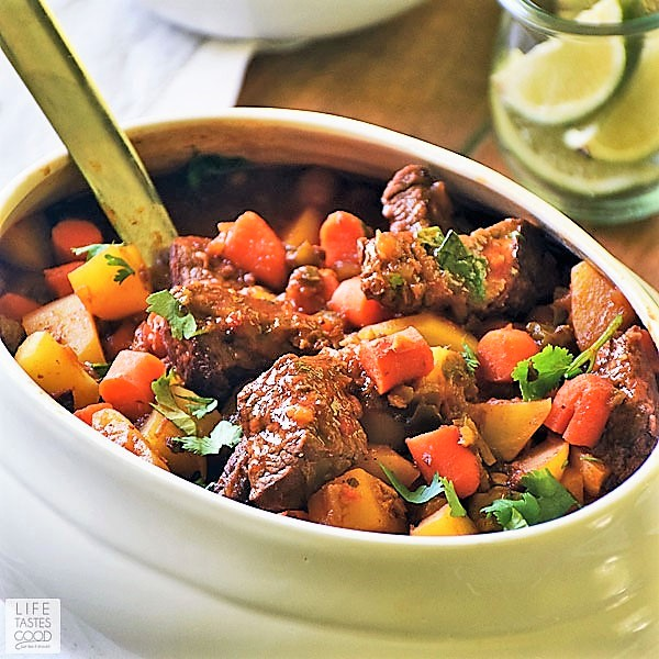 Puerto Rican Beef Stew - Carne Guisada in a white serving dish with a silver ladle