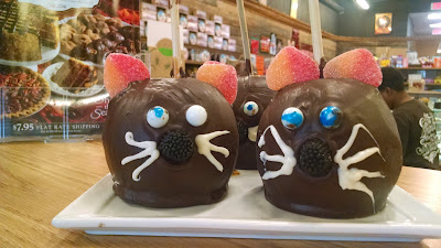 Chocolate-covered apples decorated to look like cat faces