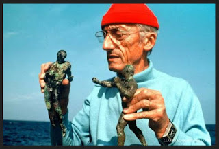 Jacques Cousteau With Recovered Artifacts From Beneath The Waves holding two antiquities of what appear to be Greek Bronzes of sportsmen or olympic athleates