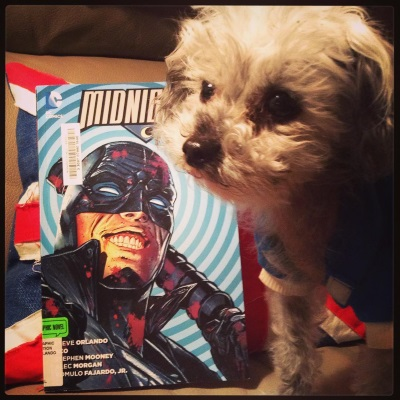 Murchie stands very close to the camera, in front of a trade paperback copy of Midnighter Volume 1. Its blue-tinted cover features a white man in a black half-mask with glowing eye holes. He's bloodsplattered and grinning.