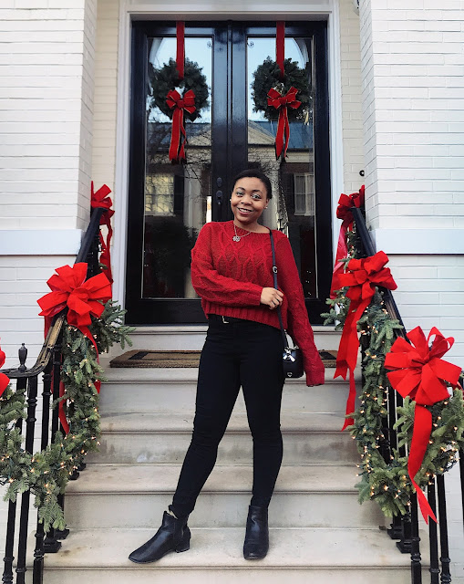 Wearing a red cable knit sweater, black skinny jeans, and black ankle boots standing on the steps of a house with 2 wreaths and red bows on the stair handle
