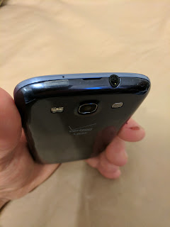 The notch at the center of the top of your S3 is where to start prying the back cover of your S3 off with, just slide your fingernail in and down the edge in each direction, eventually down the sides, too.