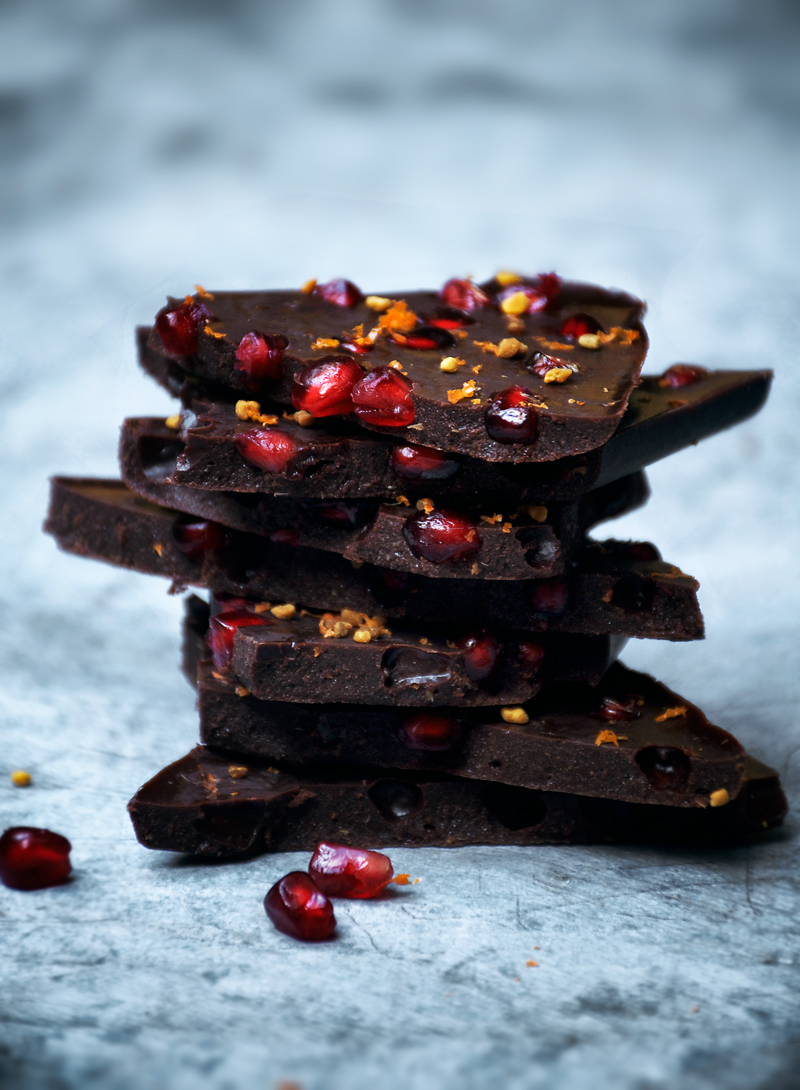 Homemade raw chocolate made with honey, pomegranate, and orange for a juicy, fruity chocolate bar. Raw chocolate has piles of health benefits and only takes a few minutes to make - this version is holiday inspired and mades a pretty food gift.
