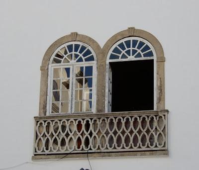 ventanales geminados sobre pared blanca y repecho entrelazado. Uno de los ventanales está abierto y en el cristal del otro se refleja un edificio
