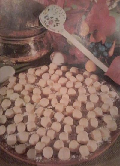 Ñoquis para acompañar con salsa de hongos. Pasta enharinada con implementos de cocina.