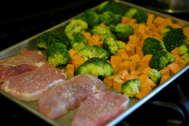 The pork chops and vegetables placed on the sheet pan.