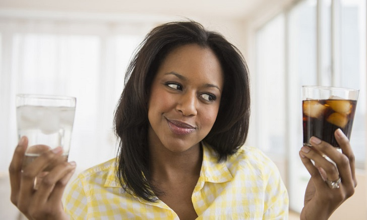 WOMAN HOLDING WATER AND SUGARY DRINK