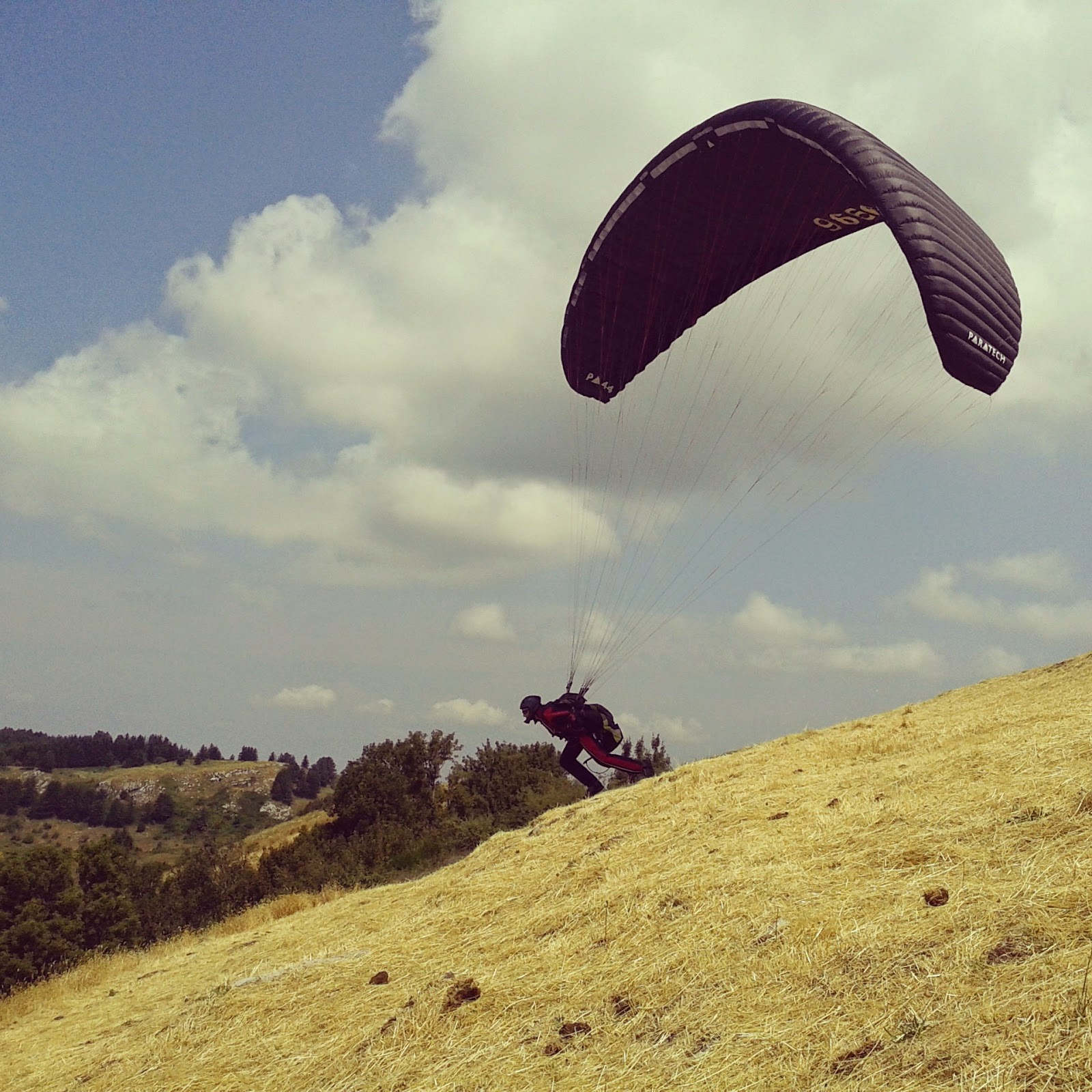 a paraglider starting from a Tuscan mountain