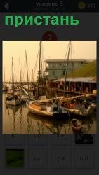 около пристани на причалах находятся несколько лодок и яхт