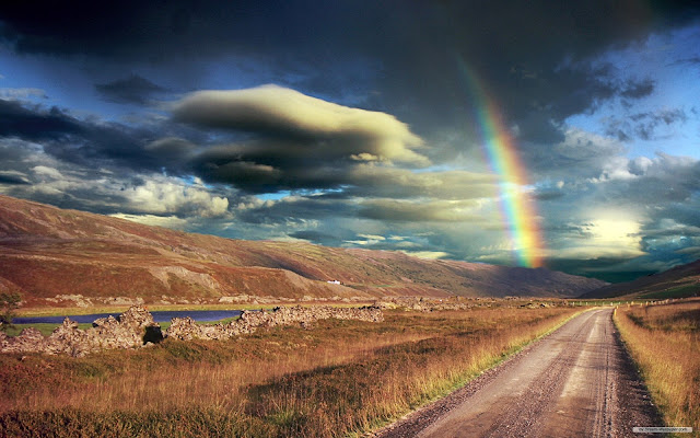 The road with breathtaking views. Clouds, sky and rainbow