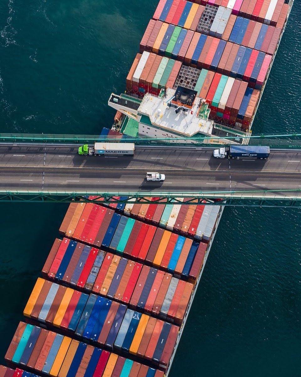 Vaixell porta-contenidors entrant o sortint de port de Los Angeles passant per sota d'un pont amb camions que també porten contenidors.