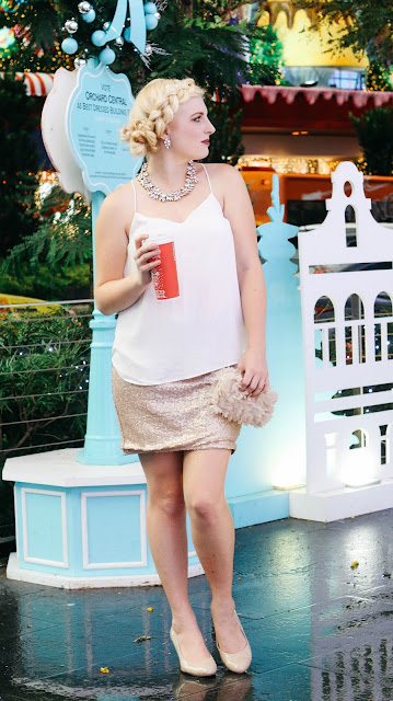 Fashion and Travel Blogger GlobalFashionGal (Brianna Degaston) wearing a J. Crew necklace and earrings, Ann Taylor top, rose gold sequined skirt, and nude heels during the Christmas time at Orchard Road in Singapore.