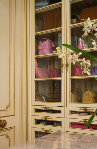 A large center island and glass-front shelves and drawers keep handbags and accessories organized.