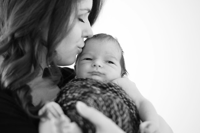 black and white photography mother kissing newborn baby