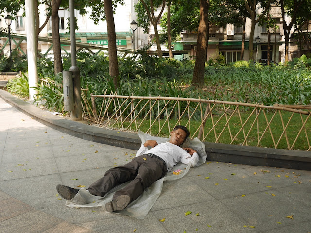 man sleeping on the ground at Lianhua Square in Foshan