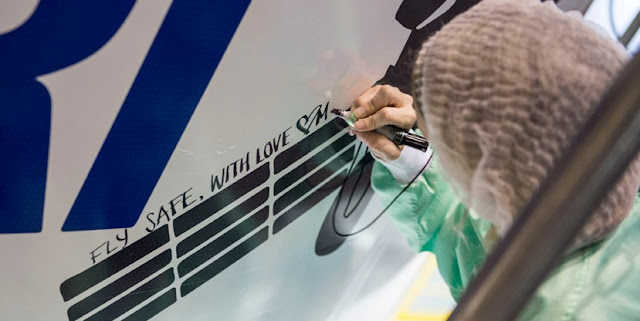 "A BRIsat satellite team member adds a ""personal touch"" to Ariane 5's payload fairing. Photo Credit: Arianespace"