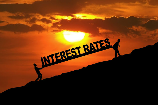 Cartoon of two people carring the words interest rates up a steep hill