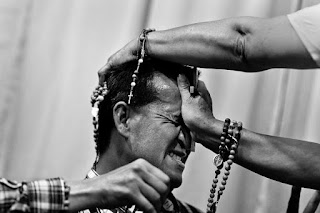 A pastor presses a crucifix on a believer's head to evict a supposed demon during an exorcism ritual.