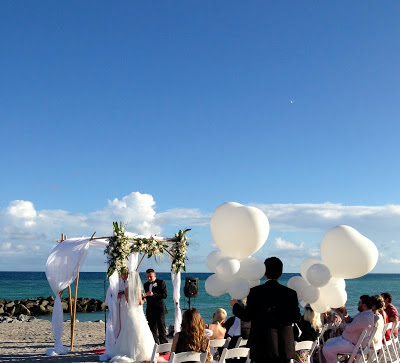 Dania beach wedding ceremony with bamboo gazebo, white folding chair