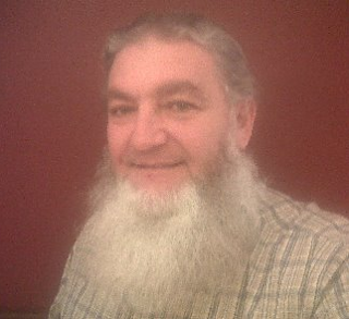 Man with a gray and white beard wearing a checked shirt and standing in front of a reddish wall