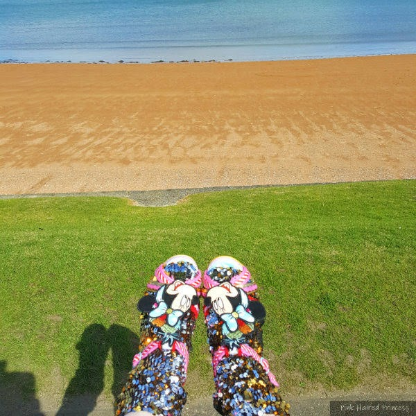 feet wearing sequins socks and Irregular Choice Minnie Mouse sandals in the sun with grass and beach in background