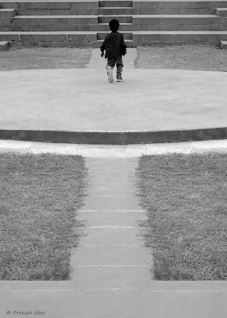 A Black and White Minimalist Photograph of a Little boy roaming around at the Open Air Amphitheater at Jawahar Kala Kendra, Jaipur.