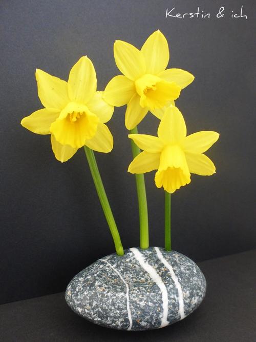 Blumendeko gelbe Narzissen vor schwarzem Hintergrund in Steinvase