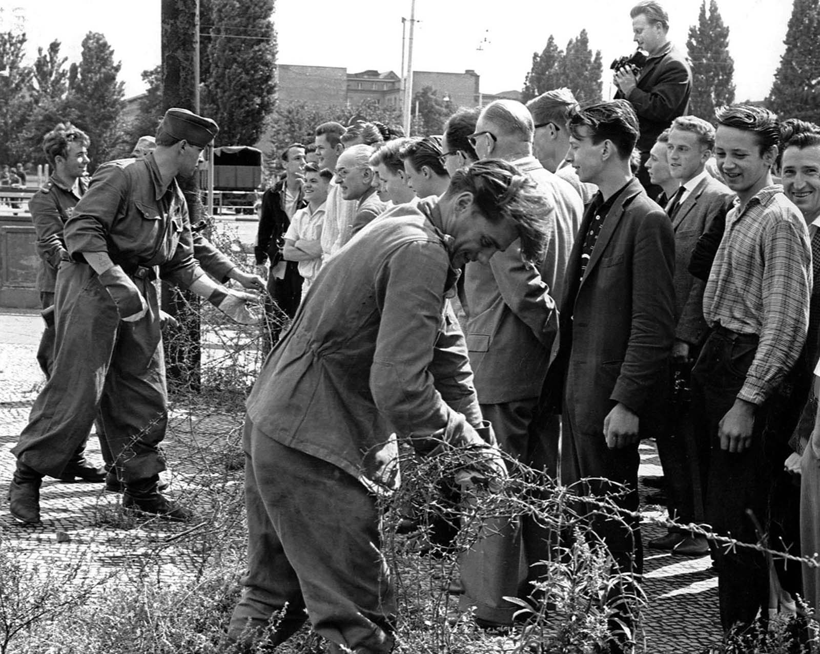 East German soldiers, left, set up barbed-wire barricades at the border separating East and West Berlin on August 13, 1961. West Berlin citizens, right, watch the work.