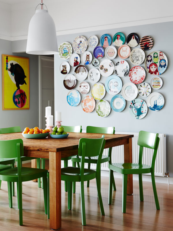 Beautiful decorative plates on wall and great green chairs in this kitchen!