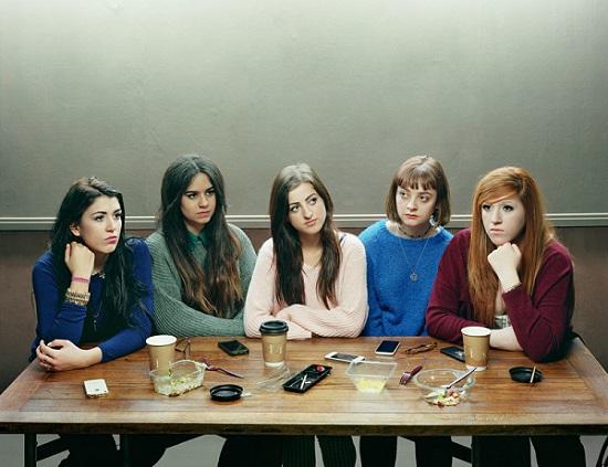 5 chicas sentadas a la mesa enajenadas unas de las otras, sus celulares frente a ellas, escena de distanciamiento social.