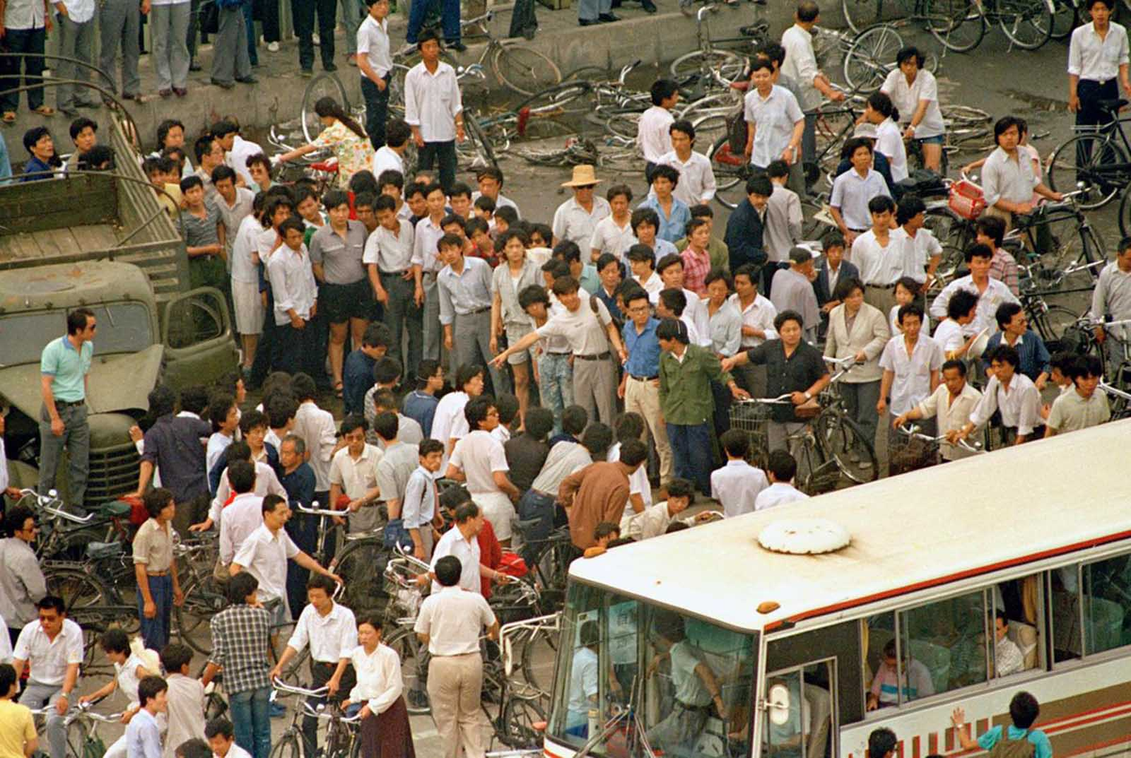 A crowd of Chinese clears a path to give a busload of foreign tourists a view of a dead body of victim of the first night of violence as People's Liberation Army troops shot their way into Tiananmen Square to crush pro-democracy protests, on Monday morning, June 5, 1989.
