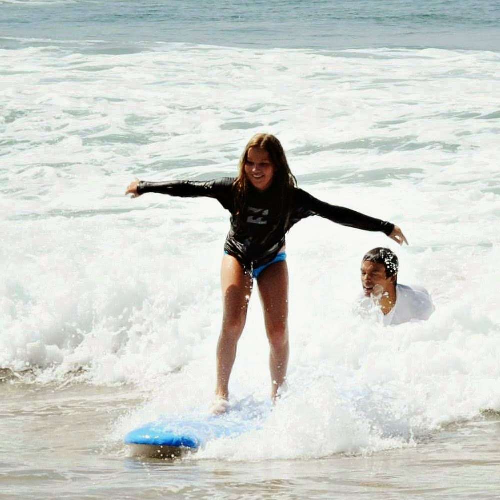 Female Aloha Beach Camp kid learns to surf at Aloha Beach Camp in Los Angeles as a camp counselor shows her how.