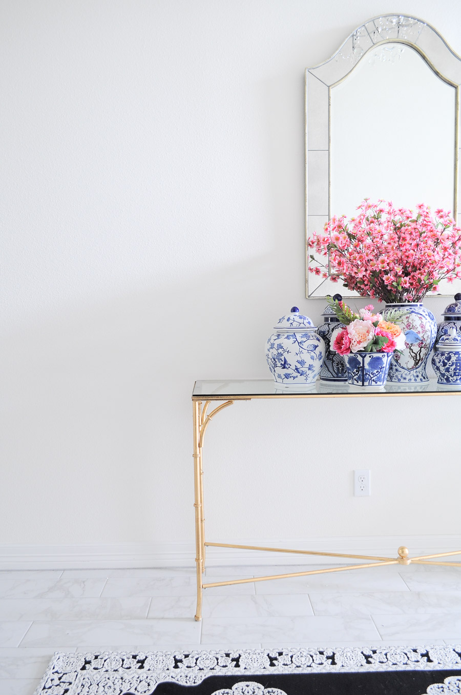 A gold bamboo foyer table and ginger jars give off classy, feminine chinoiserie vibes in this foyer.