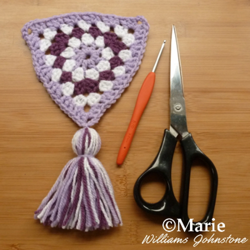 Completed section of crocheted granny triangle garland with a tassel