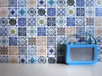 Modern one-twelfth scale miniature radio in front of a wall of random tiles in shades of blue.