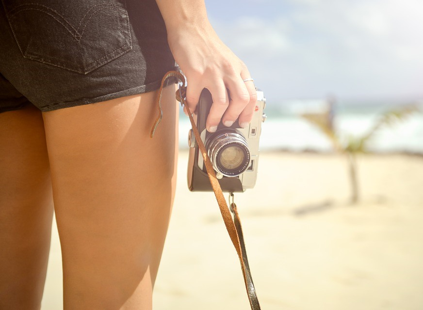 Woman in shorts without cellulite holding a camera