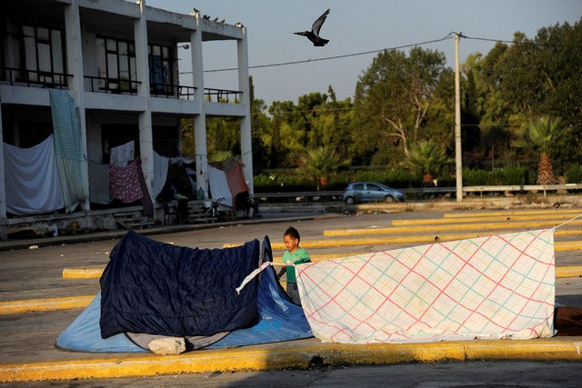 A child stands outside a tent outside the disused Hellenikon airport, where stranded refugees and migrants are temporarily accommodated in Athens, Greece, August 10, 2016. REUTERS/Michalis Karagiannis