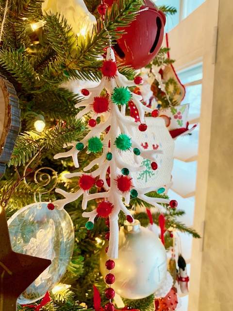 A white tree ornament hanging from a decorated Christmas tree