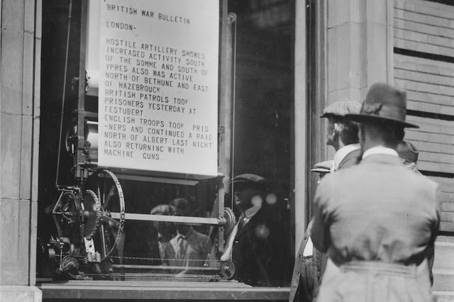 Original caption: War news printed right before your eyes is the latest method of displaying bulletins by big newspapers. The mechanical bulletin printing machines in the window of a Cincinnati newspaper. It is a linotype machine and a printing press combined.