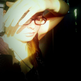 Photo of Amie, a pale skinned woman with brown hair and glasses, shading her face from the sun with her hand.